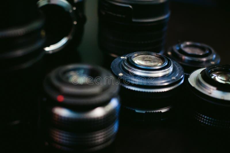 Câmera da foto DSLR com um grupo de lente retro e de flash em um fundo preto com textura de madeira fotografia de stock royalty free