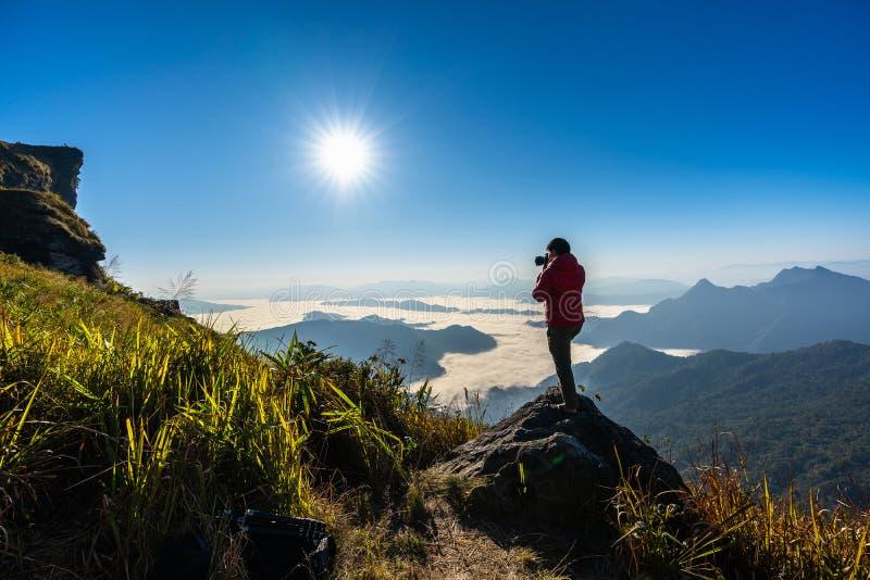 Câmera da terra arrendada da mão do fotógrafo e estar sobre a rocha na natureza conceito do curso fotos de stock royalty free