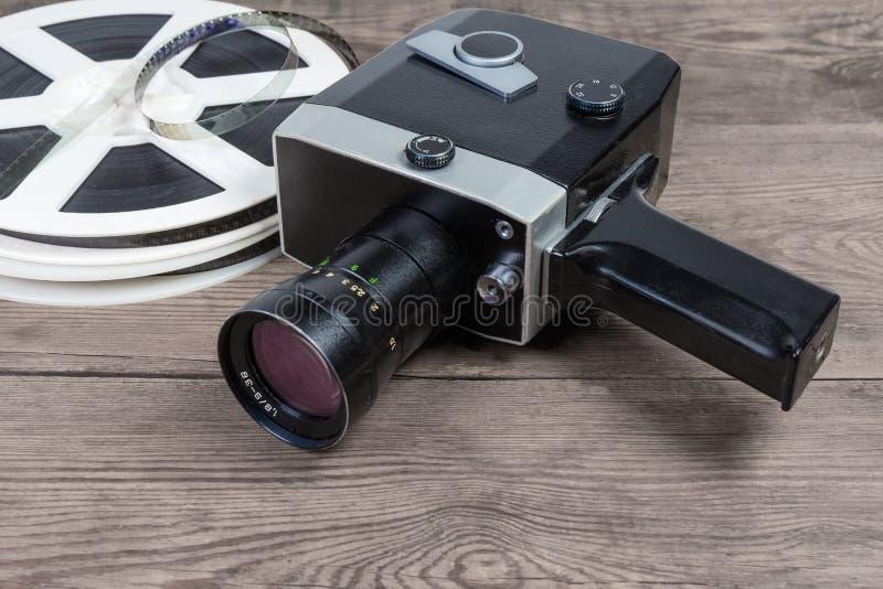 Câmera de filme amadora do vintage contra de filmes na superfície de madeira imagem de stock royalty free