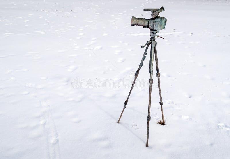 Câmera de filme com o acessório do telescópio na parte superior e o tripé na neve imagem de stock royalty free