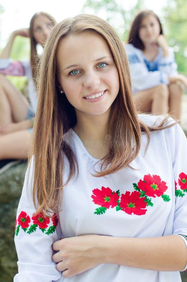 Câmera de sorriso da moça bonita & de vista feliz no fundo do verão fora foto de stock
