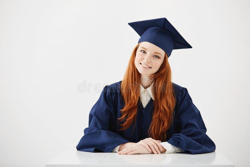 Câmera de vista de sorriso graduada da fêmea do ruivo que senta-se sobre o fundo branco foto de stock