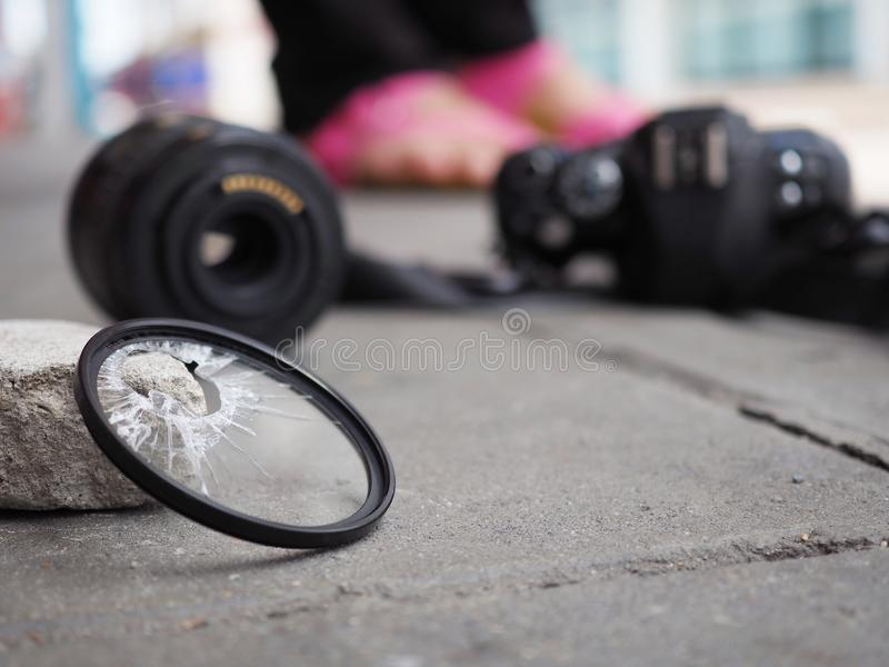 A câmera deixada cair à terra, fazendo com que o filtro quebrem, o len e o corpo danificados No conceito do seguro de acidente so foto de stock