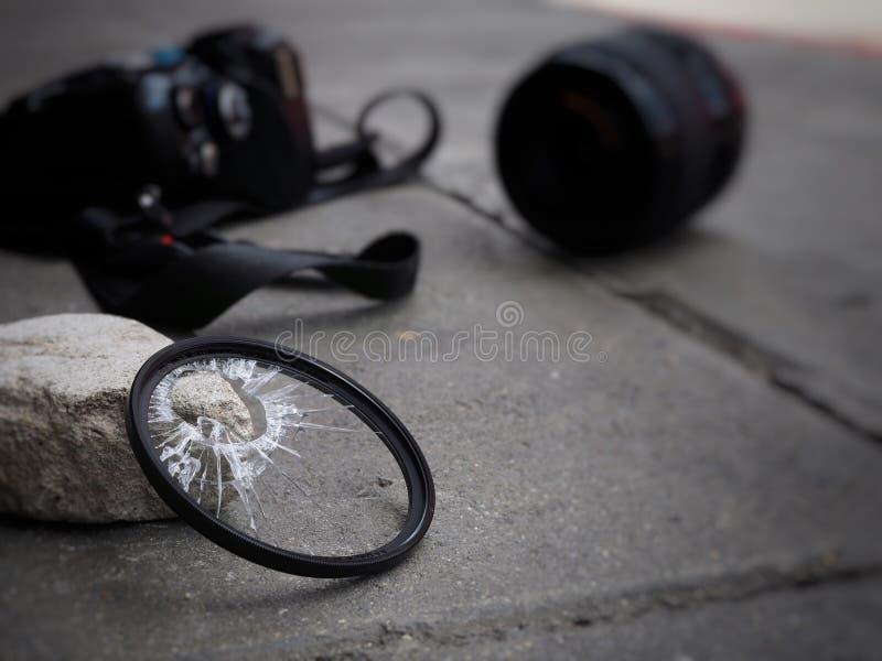 A câmera deixada cair à terra, fazendo com que o filtro quebrem, o len e o corpo danificados No conceito do seguro de acidente so foto de stock royalty free