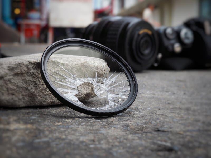 A câmera deixada cair à terra, fazendo com que o filtro quebrem, o len e o corpo danificados No conceito do seguro de acidente so imagem de stock royalty free