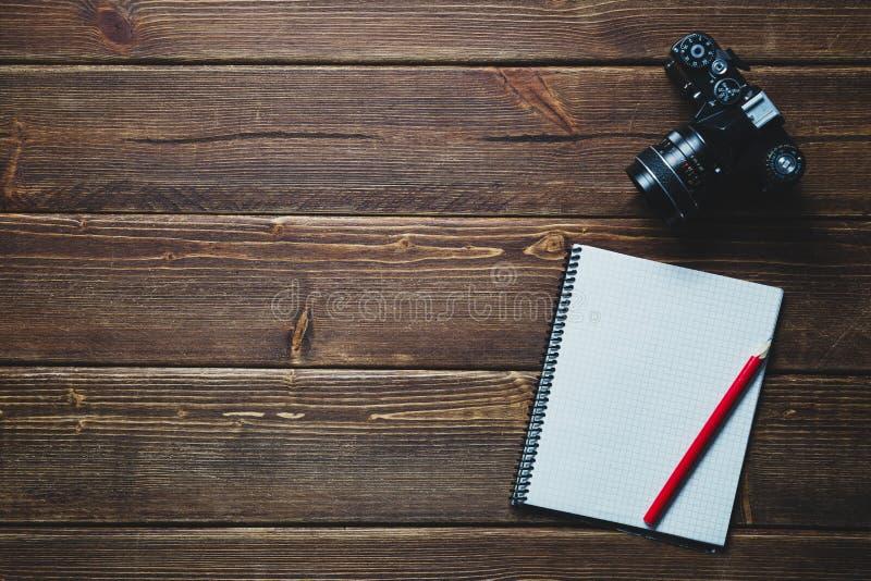 Câmera do caderno e do vintage na mesa imagens de stock