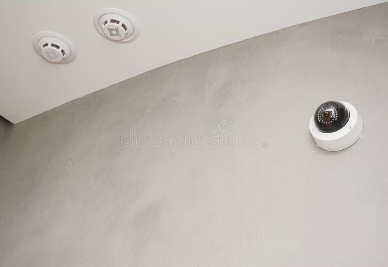 A câmera do CCTV da segurança é montada na parede da sala com sistema de alarme de incêndio, detecção de fogo imagem de stock