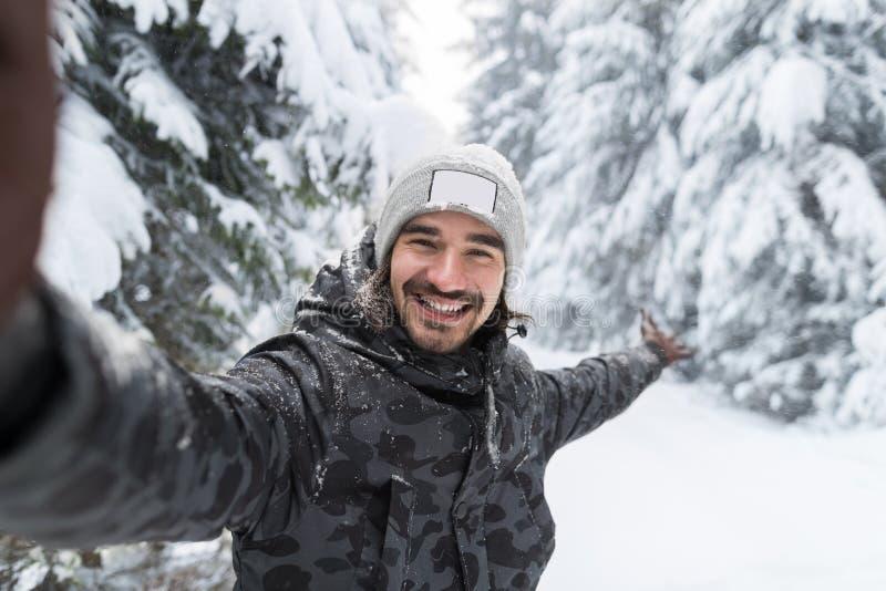 Câmera do sorriso do homem novo que toma a foto de Selfie na neve Forest Guy Outdoors do inverno imagem de stock royalty free