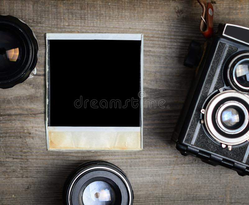 Câmera do vintage com lentes e a fotografia velha vazia no fundo de madeira fotografia de stock
