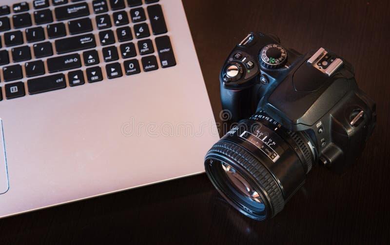 Câmera e portátil de DSLR imagens de stock