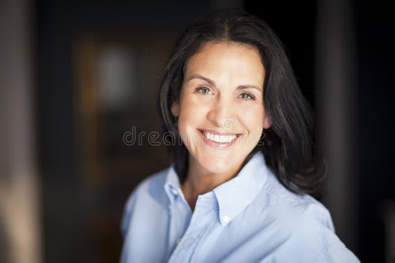 Câmera espanhola madura de Smiling At The da mulher de negócios no escritório imagens de stock royalty free