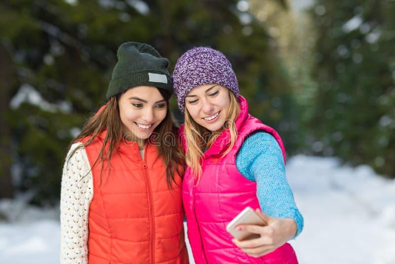 Câmera esperta do telefone da posse da menina que toma o inverno de Forest Young Woman Couple Outdoor da neve da foto de Selfie fotografia de stock