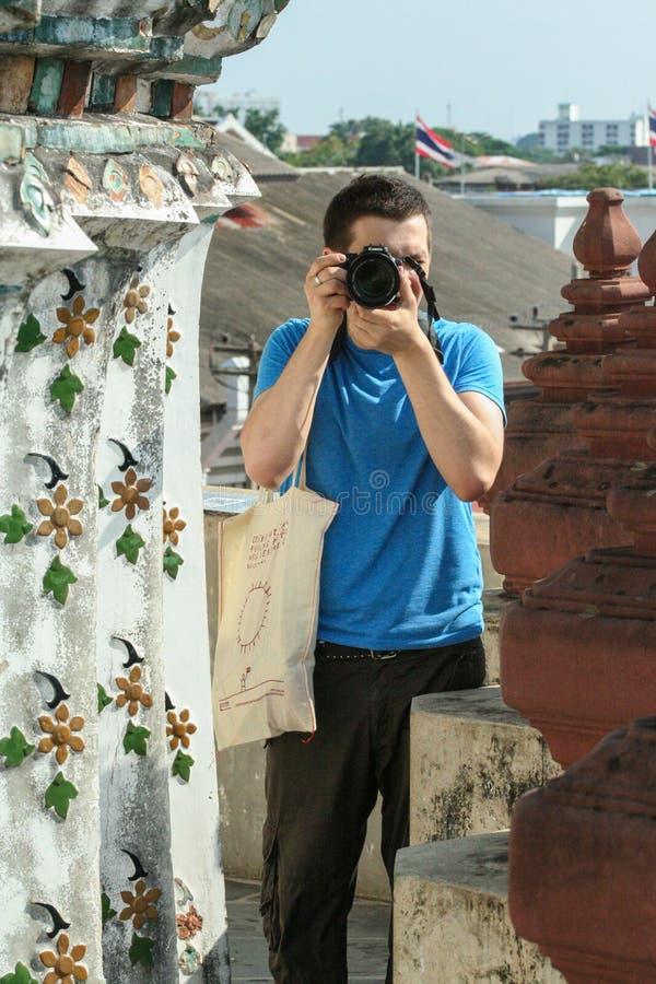 Câmera europeia da terra arrendada do turista por seus olhos Retrato de um indivíduo que dispara em um homem da câmera imagem de stock royalty free