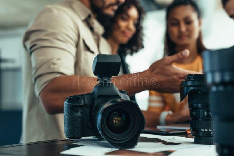 Câmera profissional e lente de DSLR na tabela com a equipe dos fotógrafo que discutem no fundo Fotógrafo que fala a foto de stock royalty free