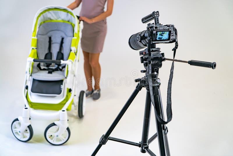 A câmera profissional está em um tripé na sala A câmera é focalizada em uma mulher no sportswear com um carrinho de criança sobre imagem de stock royalty free