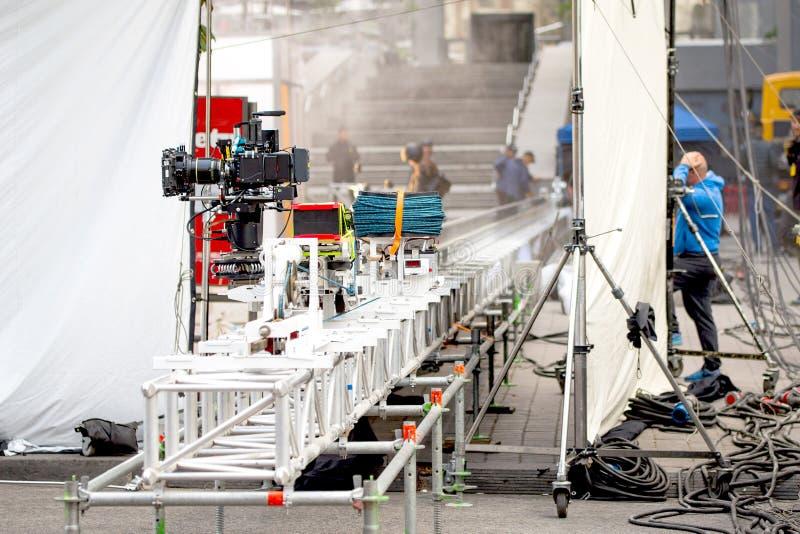 Câmera profissional grande nos trilhos Fora plateau de filmagem Cena da produção do cinema na rua da cidade Filmmakin real cândid fotos de stock royalty free