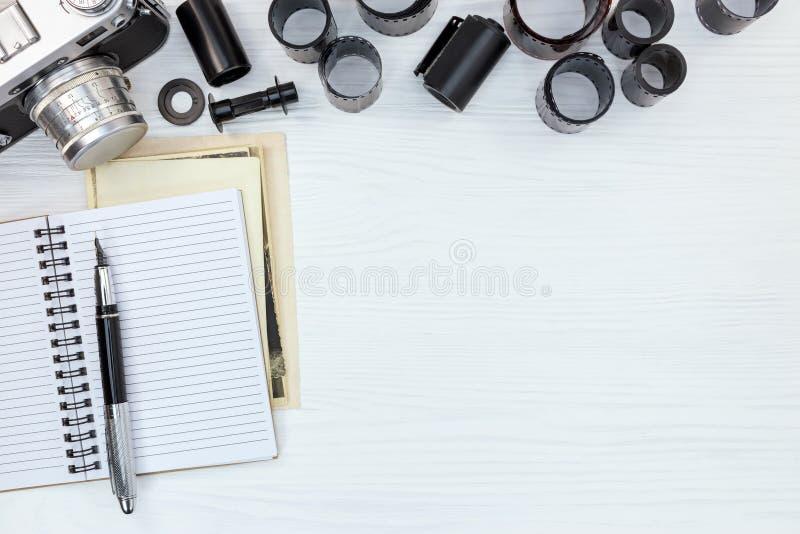 Câmera retro da foto, caderno aberto e rolos de filmes negativos no wh fotos de stock royalty free