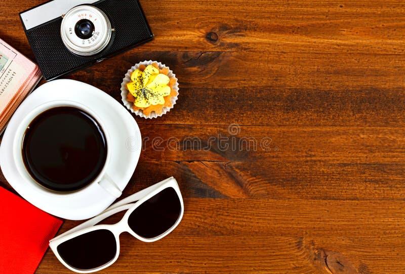 Câmera retro da foto, copo de café, passaporte, óculos de sol e queque fotos de stock