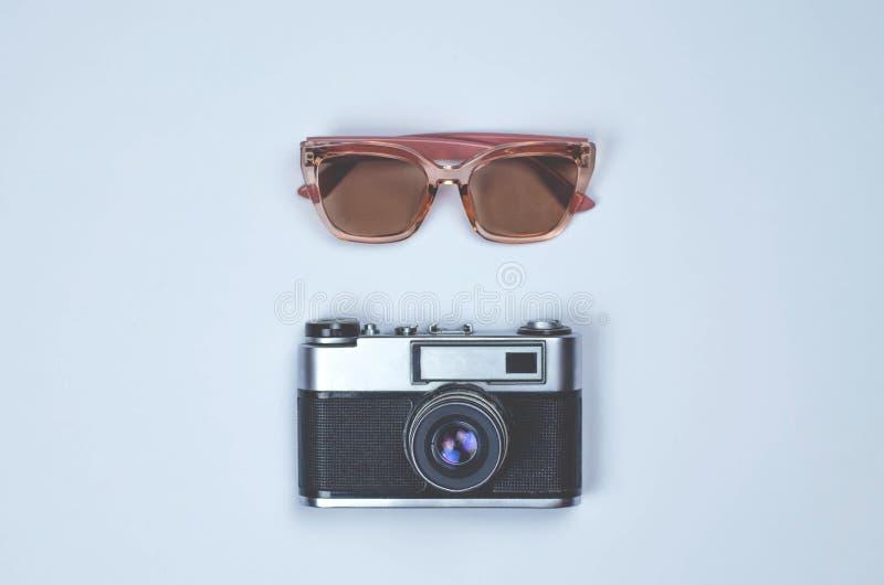 Câmera retro da foto e vidros cor-de-rosa no fundo cinzento fotografia de stock royalty free