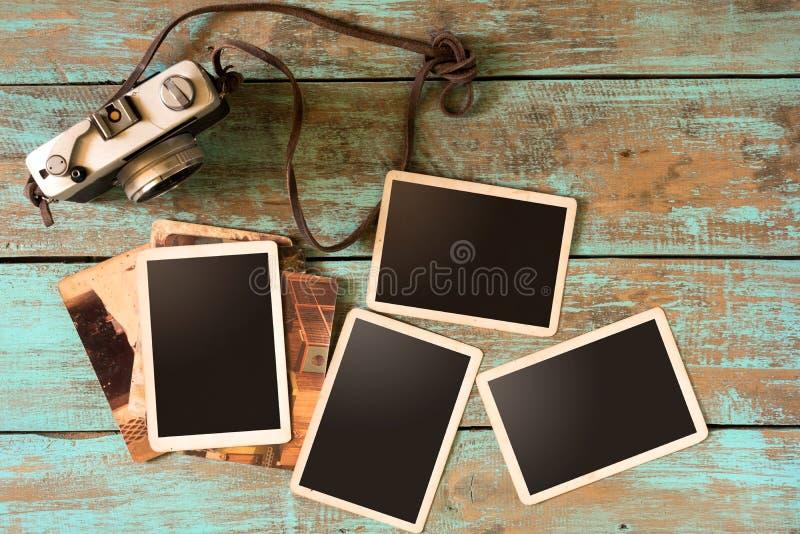 Câmera retro e álbum de fotografias de papel imediato velho vazio na tabela de madeira fotos de stock