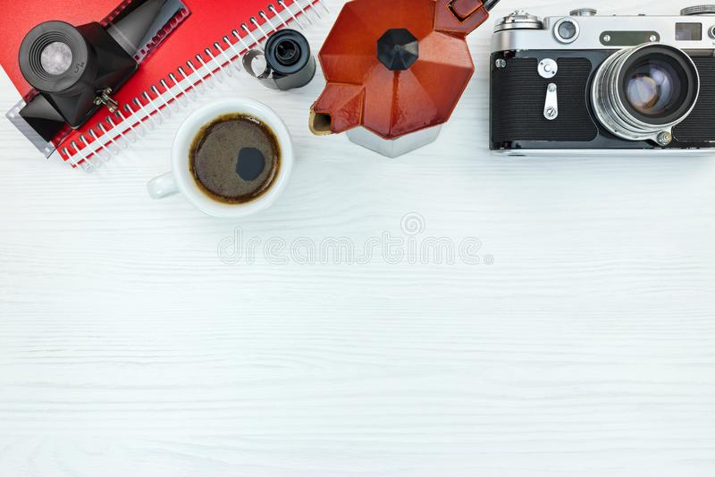 Câmera retro, filmes de rolo, lente, caderno e potenciômetro vermelho do café em w fotografia de stock