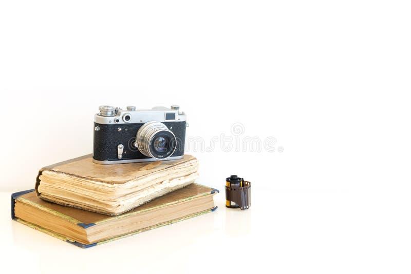 Câmera velha do filme nos livros fotografia de stock
