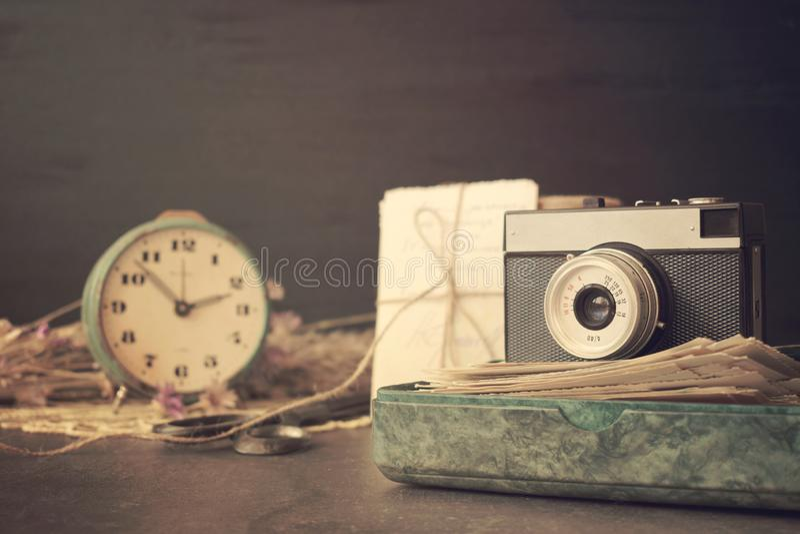 Câmera velha retro com a pilha das fotos, das letras, da caixa da malaquite e dos relógios da antiguidade no fundo de madeira Mem foto de stock