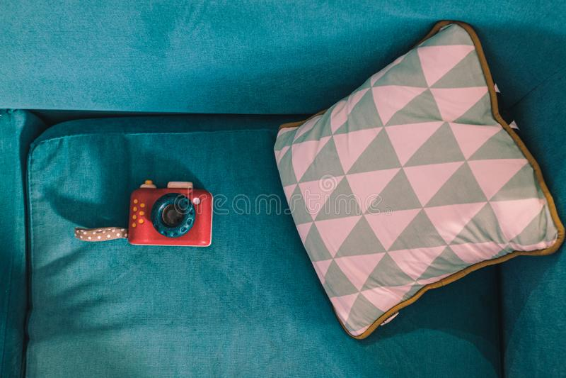 Câmera vermelha do brinquedo em um sofá verde com um descanso imagens de stock