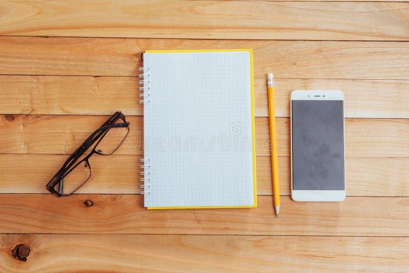 câmera, vidros e bloco de notas e lápis em um fundo de madeira marrom fotografia de stock