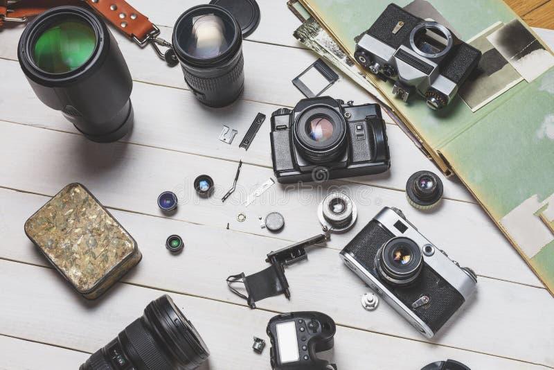 Câmeras do filme do vintage, seus componentes, câmaras digitais modernas e lentes no conce branco de madeira do desenvolvimento d imagem de stock royalty free