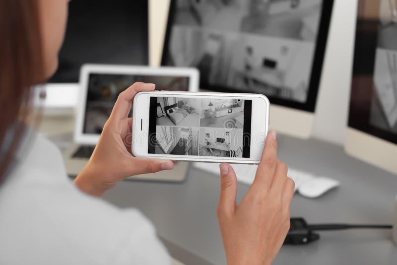 Câmeras fêmeas da casa da monitoração do agente de segurança usando o smartphone dentro imagens de stock