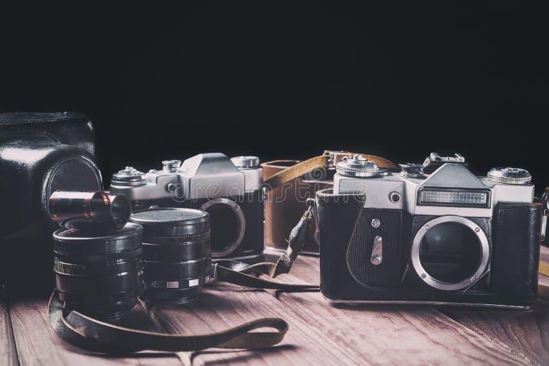 Câmeras velhas do filme com lentes e casos na madeira contra o fundo preto Foco tonificado e seletivo do vintage imagens de stock