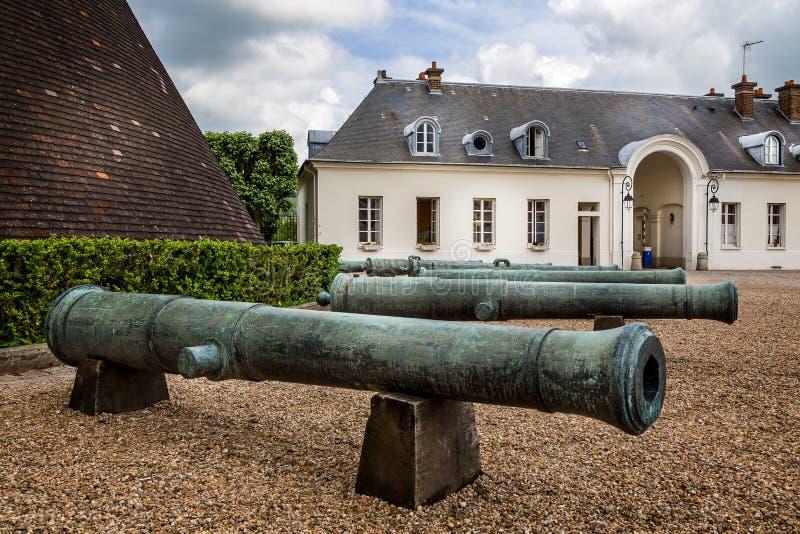 Cânones velhos na frente da grande estufa de vidraria cônica anterior no castelo Verrerie, Le Creusot, França fotos de stock