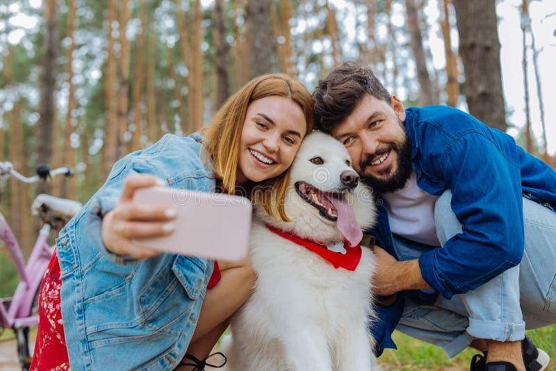 Cão branco de olhos escuros que levanta para a foto com seus proprietários foto de stock royalty free