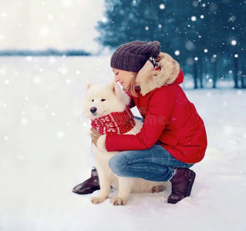 Cão branco do Samoyed do abraço feliz do proprietário da mulher no inverno foto de stock