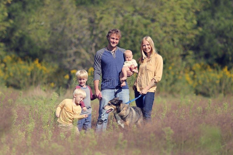 Cão de passeio da família feliz no outono imagem de stock royalty free