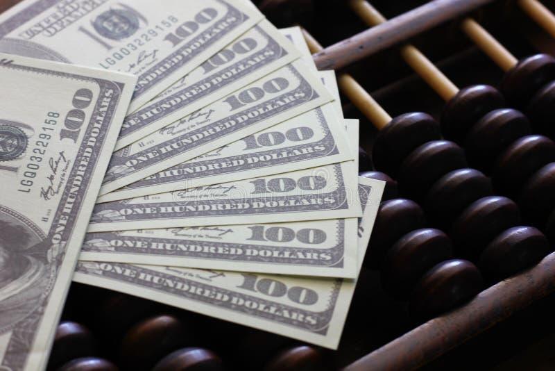Cédula americana no ábaco chinês 100 dólares com fundo do abatract fotografia de stock