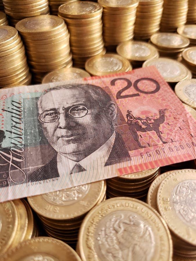 cédula australiana de vinte dólares e moedas empilhadas de dez pesos mexicanos imagem de stock royalty free