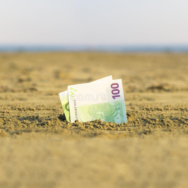 Cédula de um valor de cem euro o na areia na praia Conceito do curso e de férias baratos imagem de stock royalty free