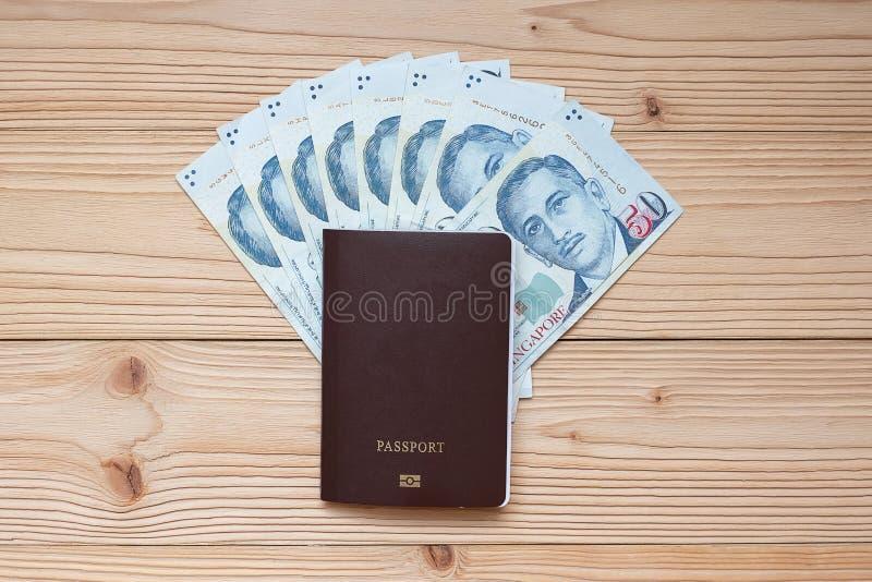 Cédula do dinheiro com o passaporte na tabela de madeira, na vista superior e no espaço da cópia Hora de viajar no conceito de Si imagem de stock royalty free