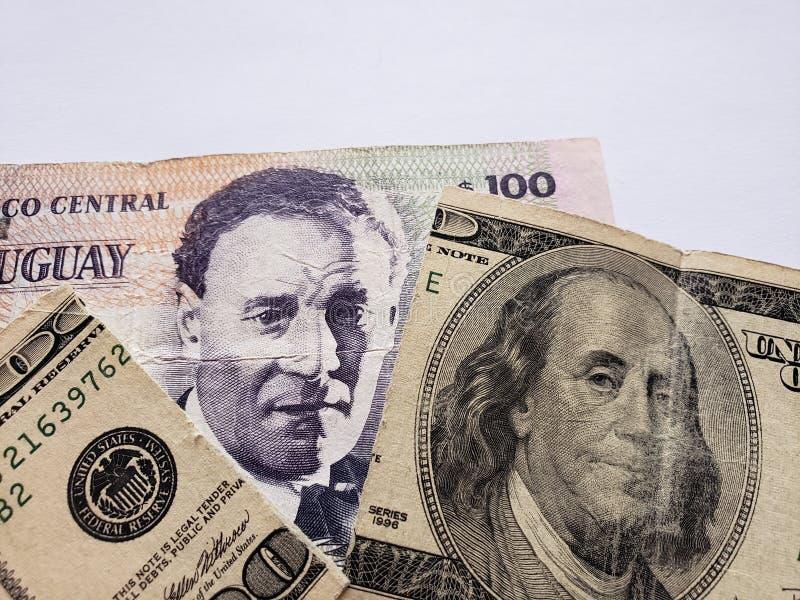 cédula uruguaia de 100 pesos e cédula americana quebrada de 100 dólares imagem de stock