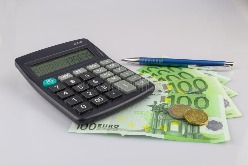 100 cédulas das contas do euro euro- e dinheiros das moedas com calculadora e pena Moeda da Uni?o Europeia Fundo isolado imagem de stock