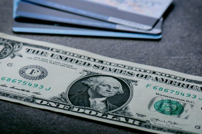 Cédulas de um dólar em uma tabela preta com cartões de crédito Dólares do americano do dinheiro do dinheiro Fundo do vintage Alar imagem de stock