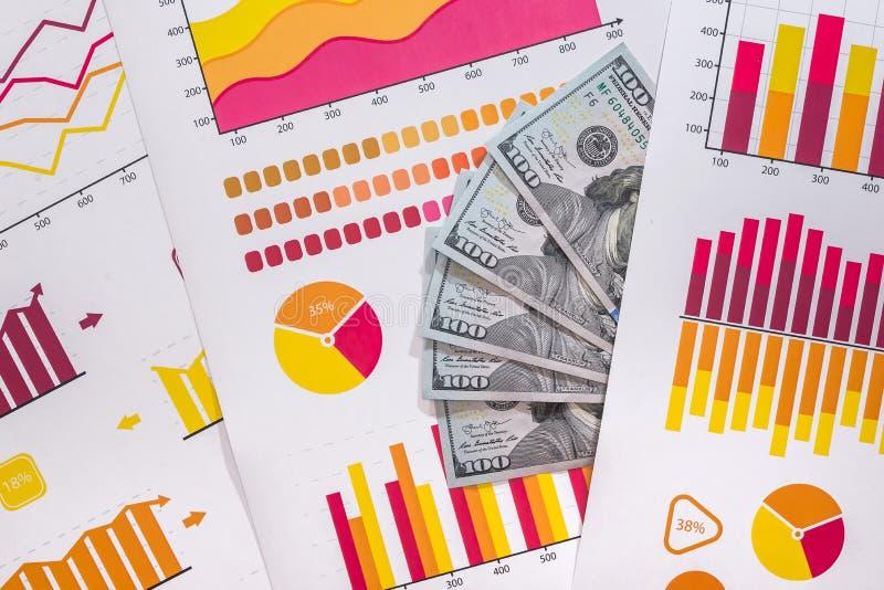 Cédulas do dólar com gráficos de negócio coloridos fotos de stock