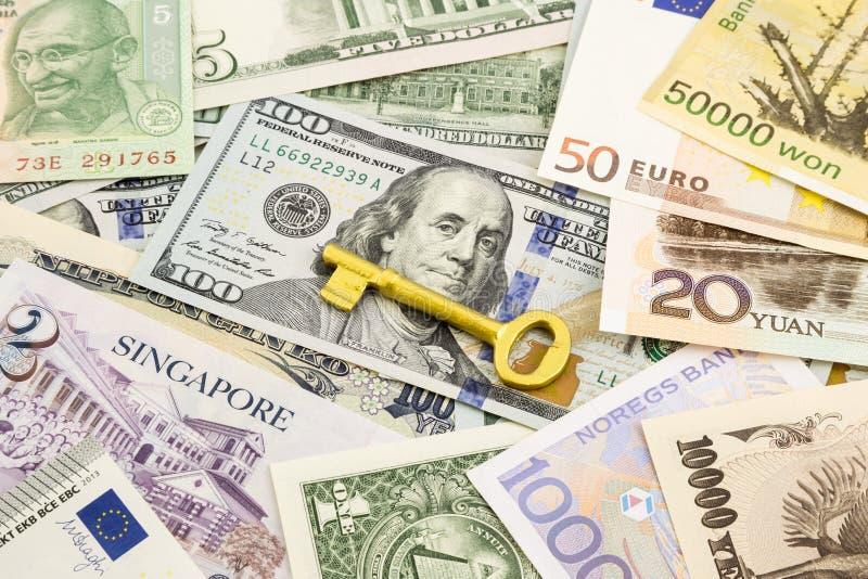 Cédulas do dinheiro da moeda da chave dourada e do mundo fotos de stock royalty free