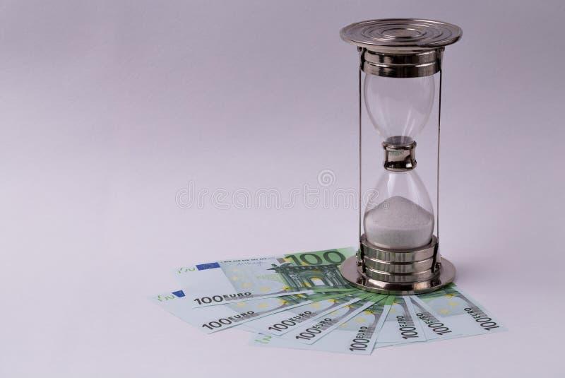 Cédulas do EURO e uma ampulheta em um fundo branco Tempo é dinheiro conceito fotos de stock