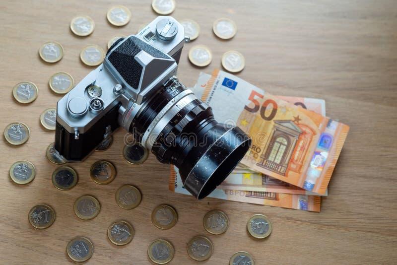 Cédulas do Euro, moedas e uma câmera em um fundo de madeira claro fotos de stock royalty free