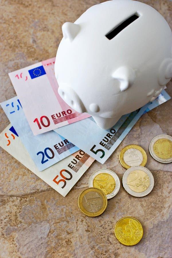 Cédulas e moedas do Euro com mealheiro fotografia de stock royalty free