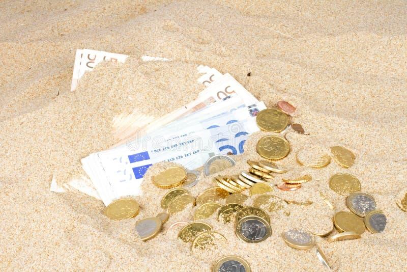 Cédulas e moedas do Euro na areia imagem de stock
