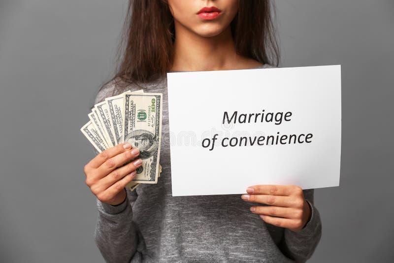 Cédulas e papel do dólar da terra arrendada da jovem mulher com UNIÃO do texto DE CONVENIÊNCIA no fundo cinzento imagem de stock royalty free